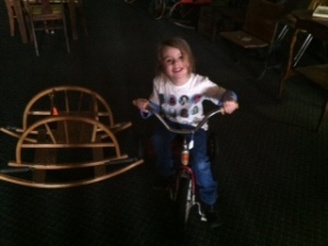 Riding a really old tricycle at the thrift store...wearing her Star Wars shirt, of course.